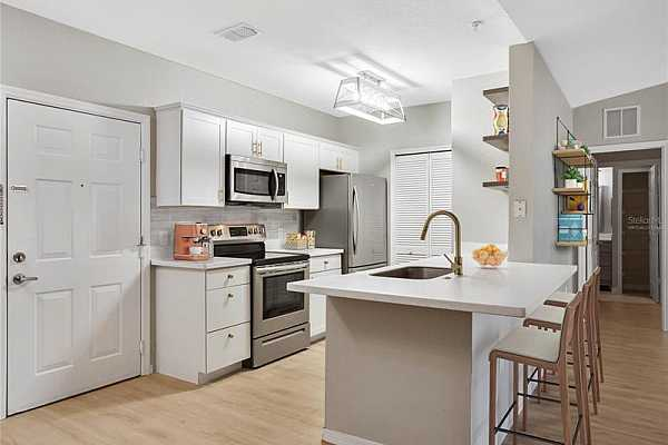 Photo #8 The home chef will delight in this bright and airy KITCHEN that features MODERN CABINETS with GOLD HARDWARE, GOLD FAUCET, STAINLESS STEEL APPLIANCES, TILED BACKSPLASH, QUARTZ COUNTERS and even a BREAKFAST BAR! Virtually Staged