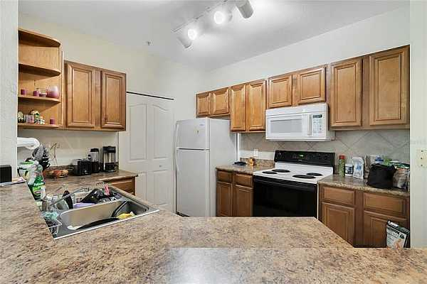 Photo #8 The KITCHEN is fully equipped with quality appliances, ample cabinet storage, closet pantry and a breakfast bar.