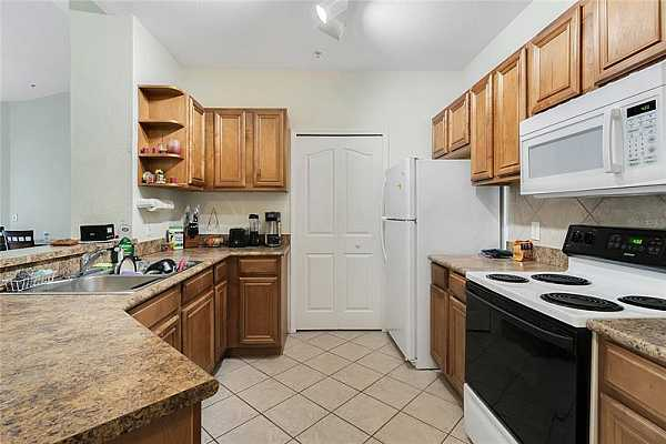 Photo #9 The KITCHEN is fully equipped with quality appliances, ample cabinet storage, closet pantry and a breakfast bar.