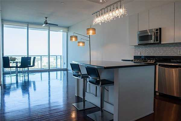 Photo #10 Spacious kitchen and living room leading to private balcony!